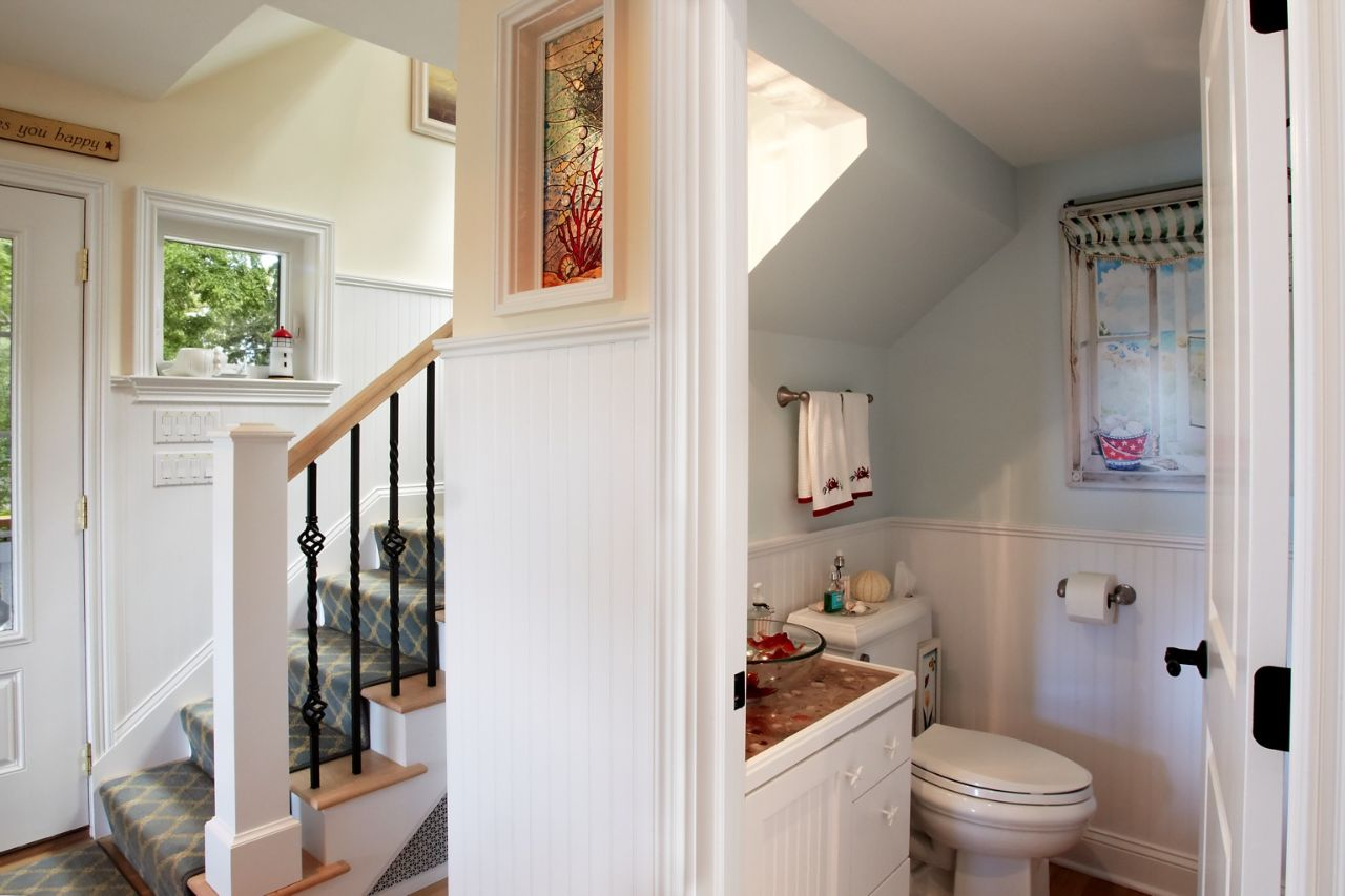 Half bath tucked under stairway